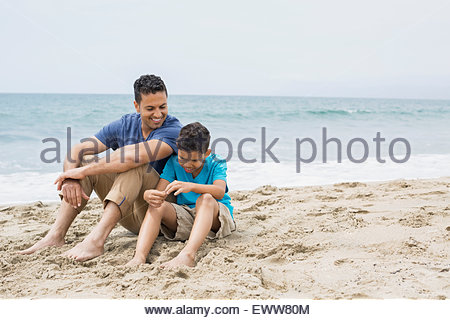 Father and son sitting on beach - Stock Photo