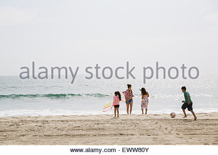 Family playing on beach and wading in ocean - Stock Photo
