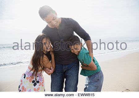 Portrait family hugging on sunny beach - Stock Photo