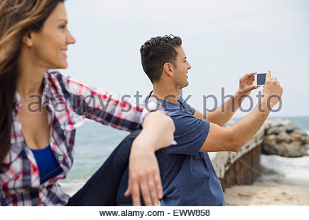 Man photographing with camera phone at beach - Stock Photo