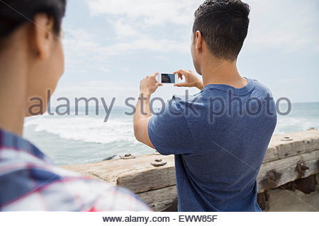 Man photographing ocean with camera phone at beach - Stock Photo