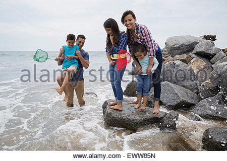 Family on rocks playing in ocean - Stock Photo