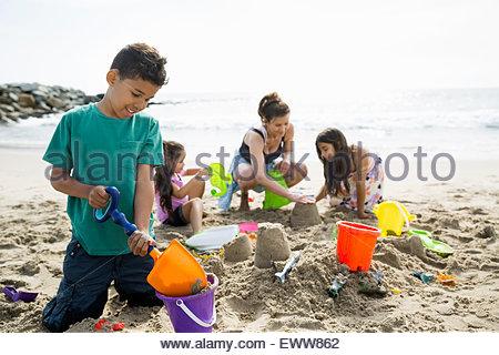 Family making sandcastle on sunny beach - Stock Photo