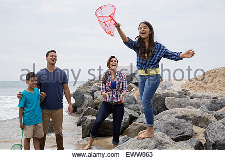 Family watching girl with fishing net ocean rocks - Stock Photo