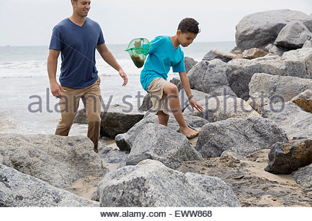 Father and son with fishing net ocean rocks - Stock Photo