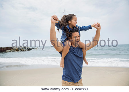 Playful father carrying daughter on shoulders at beach - Stock Photo