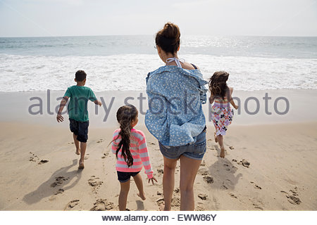 Family running toward ocean on sunny beach - Stock Photo