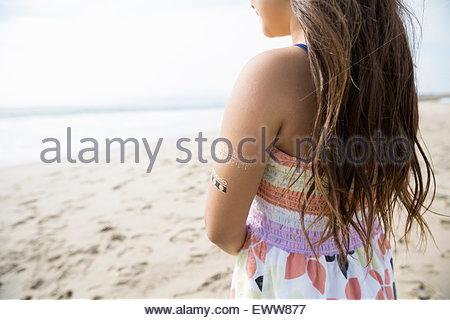 Pensive girl with henna tattoos on arm beach - Stock Photo