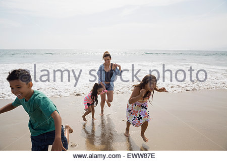 Family running from ocean onto sunny beach - Stock Photo