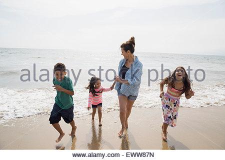 Family running along ocean surf on sunny beach - Stock Photo