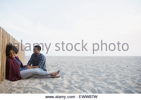 Couple relaxing against beach wall - Stock Photo