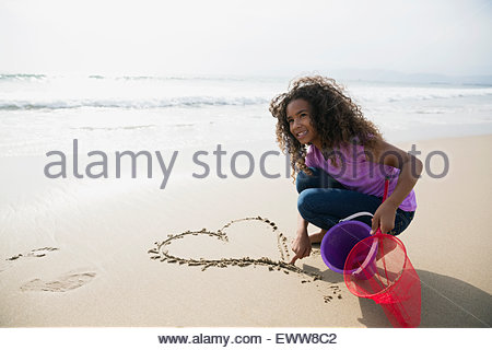 Girl drawing heart-shape in sand on beach - Stock Photo