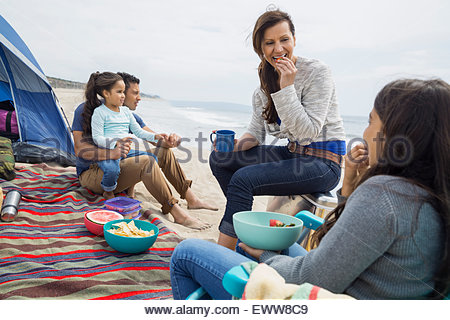 Family picnicking outside tent on beach - Stock Photo