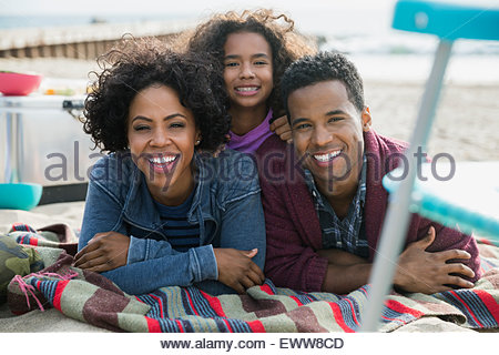 Portrait smiling family laying on beach - Stock Photo