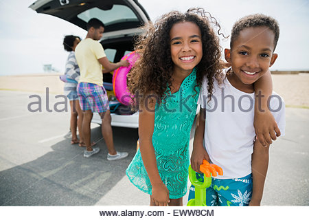 Portrait enthusiastic brother and sister arriving at beach - Stock Photo