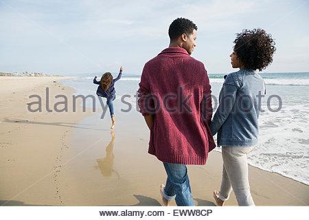 Family walking on sunny beach - Stock Photo