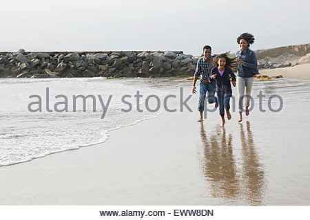 Family running on beach - Stock Photo