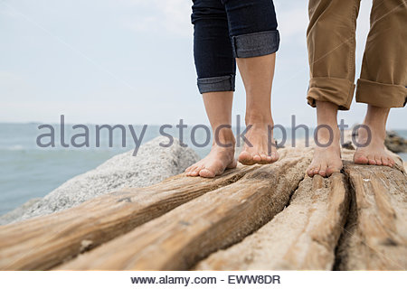 Close up bare feet of couple on ocean jetty - Stock Photo