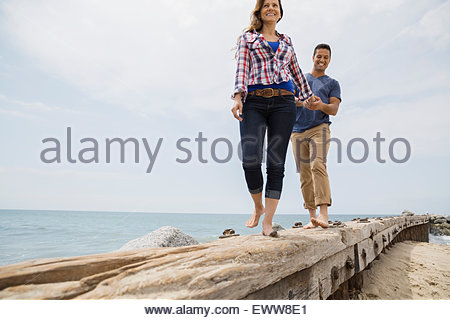 Couple walking along jetty at ocean - Stock Photo