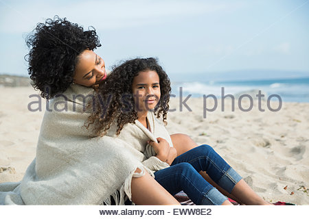 Mother and daughter wrapped in blanket on beach - Stock Photo