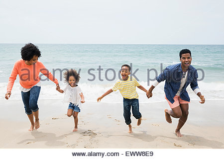 Family holding hands and running on beach - Stock Photo