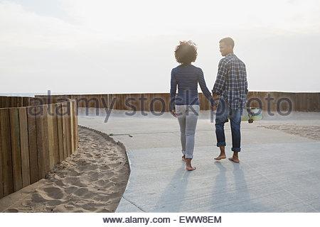 Couple walking on beach path - Stock Photo