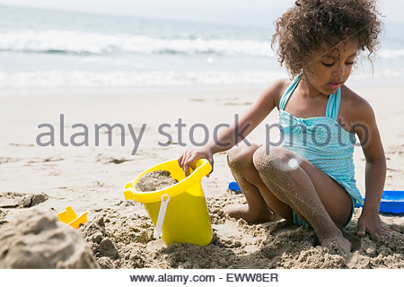 Girl in bathing suit making sandcastle on beach - Stock Photo