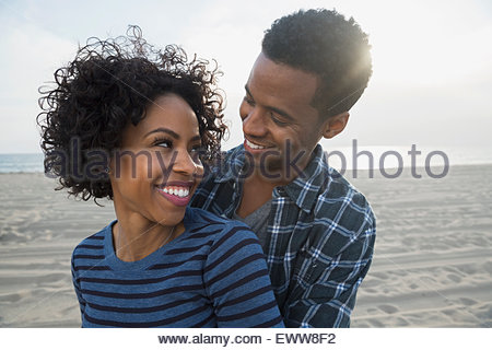 Affectionate couple hugging on sunny beach - Stock Photo