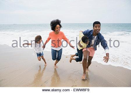 Playful family running on beach - Stock Photo