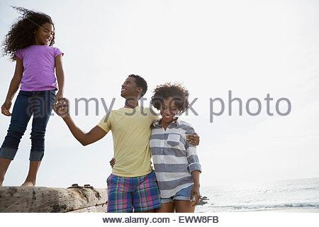 Family walking along beach wall - Stock Photo