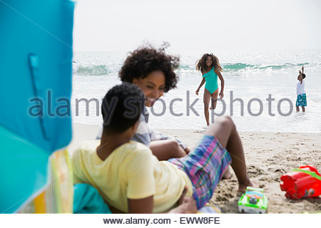 Family playing and relaxing on beach - Stock Photo