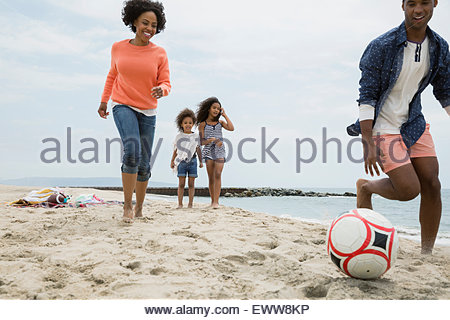 Family playing soccer on beach - Stock Photo