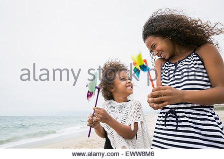 Sisters holding pinwheels on windy beach - Stock Photo