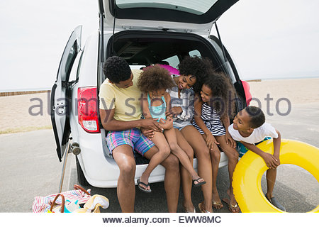 Family sitting in car hatchback at beach - Stock Photo