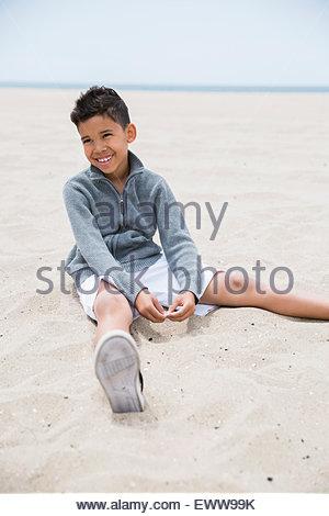 Smiling brunette boy sitting on beach - Stock Photo
