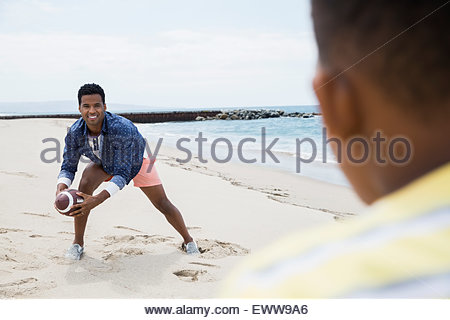 Father and son playing with football on beach - Stock Photo