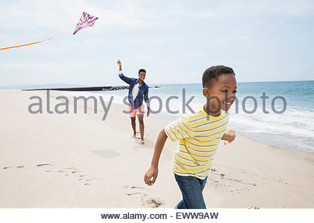 Father and son flying kite on beach - Stock Photo