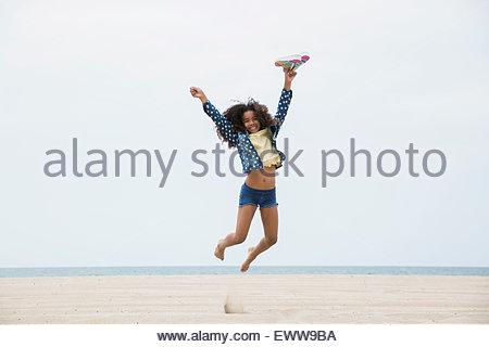 Portrait exuberant girl jumping on beach - Stock Photo