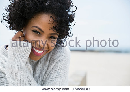 Portrait smiling woman curly black hair at beach - Stock Photo