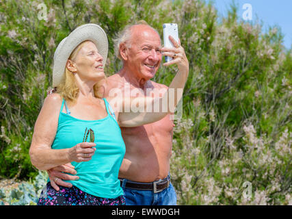 Elderly couple taking a selfie photo of themselves on a hot sunny day in Summer in the UK. Happy elderly couple. - Stock Photo