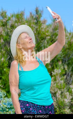 Middle aged woman taking a selfie photo of herself on a hot sunny day in Summer in the UK. - Stock Photo