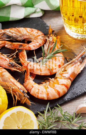 Grilled shrimps on stone plate and beer mug on wooden table - Stock Photo