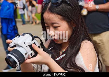 Pretty Asian woman examining screen on SLR digital camera - Stock Photo