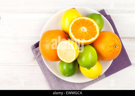 Citrus fruits on plate. Oranges, limes and lemons. Over wooden table background - Stock Photo
