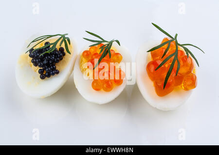 Trout, salmon and sturgeon caviar served on quail eggs, top view - Stock Photo