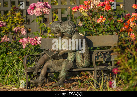 Bronze Max Turner sculpture of a boy and girl reading on a bench located in a flower garden - Stock Photo