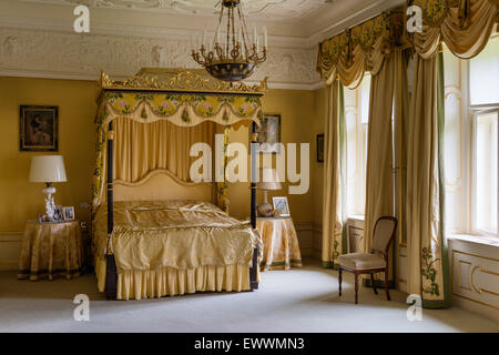 Four poster bed with gilt framework in sumptous bedroom with stucco ceiling and floor-length curtains - Stock Photo