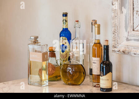 Assorted bottles of colorful liquor on table - Stock Photo