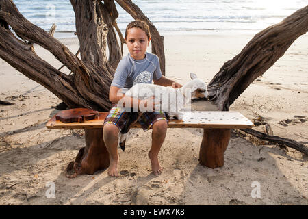 A young man sits on a handmade wooden bench with a lamb on his lap at a Costa Rican beach in Guanacaste - Stock Photo