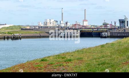 View on IJmuiden Steelworks ( Hoogovens ) left, and bridge across Zuidersluis ( Southern lock ), North Holland, - Stock Photo